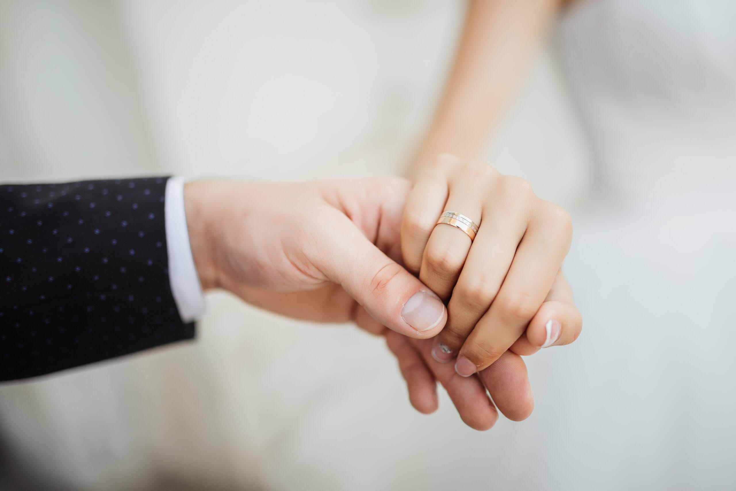 mains de jeunes mariés avec alliances